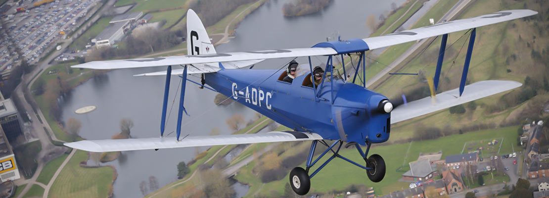 Tiger moth flying over town