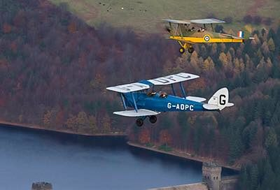 2 tiger moths in formation over a dam